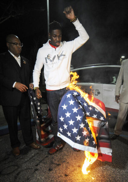 "Activist Carlos Chaverst Jr., center, drops a burning U.S. flag during a protest against the police shooting of a black man in an Alabama shopping mall in Hoover, Ala., Tuesday, Feb. 5, 2019. Demonstrators are upset with the state's decision against prosecuting a police officer who shot and killed Emantic ""EJ"" Bradford Jr. in a shopping mall on Thanksgiving night. (AP Photo/Jay Reeves)"