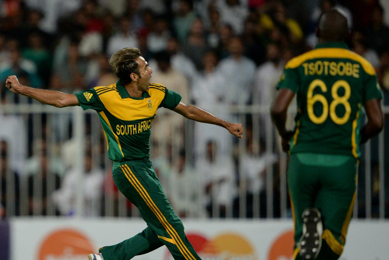South African bowler Imran Tahir (L) celebrates after taking a wicket of Pakistan's cricketer Wahab Riaz (unseen) in Sharjah Cricket Stadium in Sharjah on October 30, 2013. South African captain AB de Villiers won the toss and decided to bat in the first of five one-day internationals against Pakistan in Sharjah. AFP PHOTO/ Asif HASSAN        (Photo credit should read ASIF HASSAN/AFP/Getty Images)
