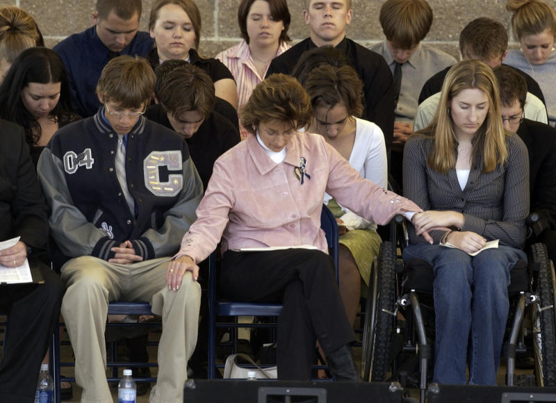 Anne Marie Hochhalter (right) prays during an event to remember those lost during the Columbine attack. She says she became disillusioned with her lawmakers over time. (Hyoung Chang via Getty Images)