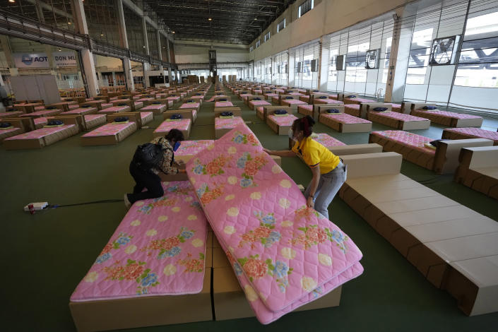 A volunteer and a worker prepare a 1,800-bed field hospital set up inside a cargo building in Don Mueang International Airport in Bangkok, Thailand, Thursday, July 29, 2021. Health authorities raced on Thursday to set up yet another large field hospital in Thailand's capital as the country recorded a new high in COVID-19 cases and deaths. The hospital, one of many already in use, was being set up at one of Bangkok's two international airports after the capital ran out of hospital beds for thousands of infected residents. (AP Photo/Sakchai Lalit)
