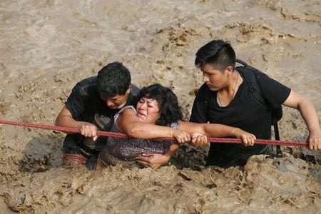 A woman is assisted while crossing a flooded street after the Huayco river overflooded its banks sending torrents of mud and water rushing through the streets in Huachipa