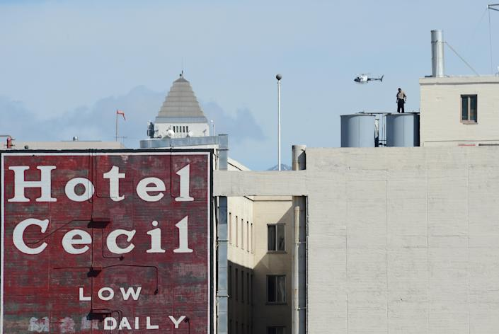 A worker stands on a water tank on the roof of the Hotel Cecil in Los Angeles California February 20, 2013. The body of 21-year-old Canadian tourist Elisa Lam was found in a water tank on the roof of the hotel three weeks after she went missing, police said. The corpse was found February 19 after hotel guests complained of low water pressure.  AFP PHOTO Robyn BECK        (Photo credit should read ROBYN BECK/AFP via Getty Images)