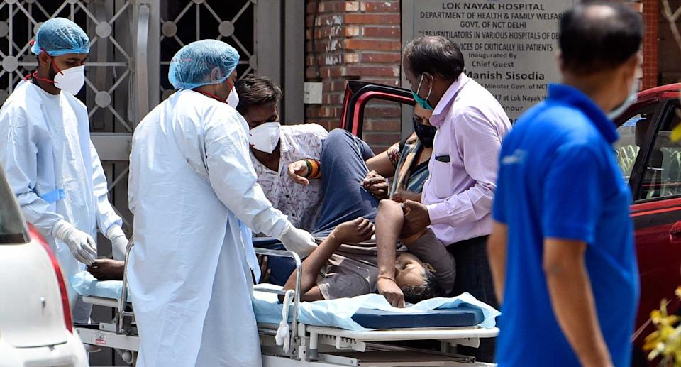 Health workers move a  Covid-19 patient at Lok Nayak Jai Prakash (LNJP) Hospital, this week in New Delhi. Source: Getty