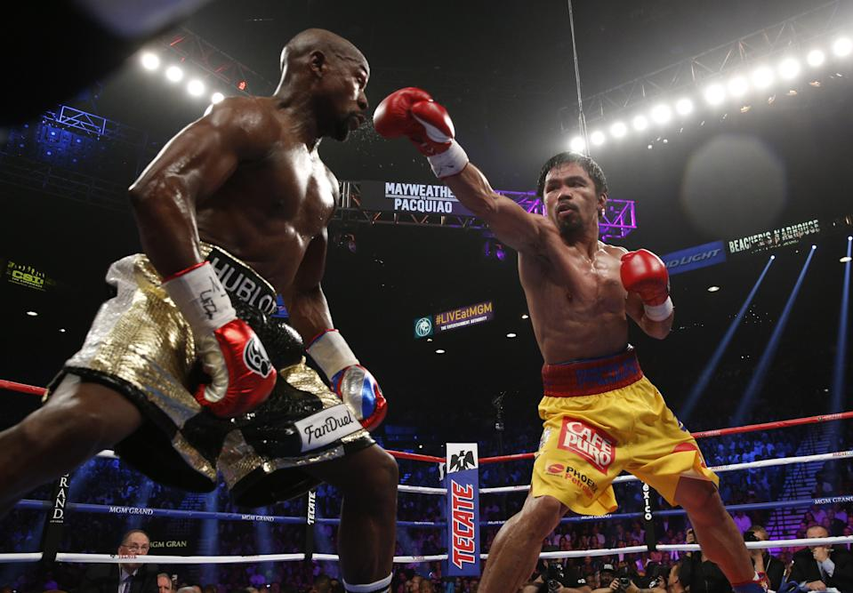 FILE PHOTO: Floyd Mayweather Jr. exchange punches with Manny Pacquiao during their welterweight unification championship bout, May 2, 2015 at MGM Grand Garden Arena in Las Vegas, Nevada. (Photo: JOHN GURZINSKI/AFP via Getty Images)