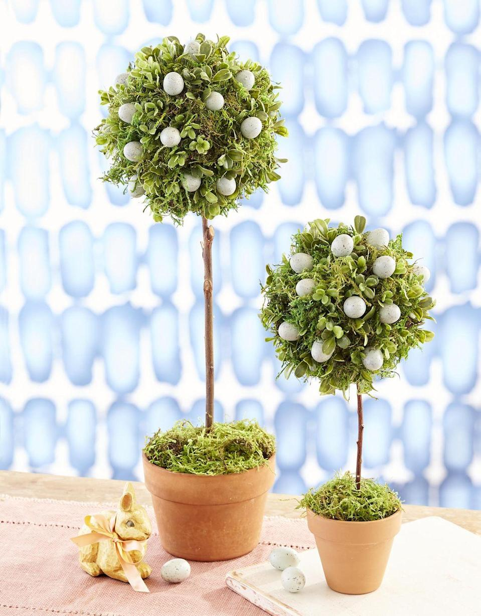 """<p>Made from moss and faux boxwood, these topiaries make the perfect focal point for your Easter table.</p><p><strong>T</strong><strong><strong>o make:</strong></strong> Using hot-glue, attach preserved green sheet moss and fake mini boxwood greenery to a round Styrofoam ball until covered. Nestle faux robin's eggs in moss, attaching with glue. Fill a clay pot with floral foam. Poke a stick into bottom of topiary, and insert into floral foam; cover foam with moss.</p><p><a class=""""link rapid-noclick-resp"""" href=""""https://www.amazon.com/Speckled-Easter-Crafts-Filler-Country/dp/B08NCFFZSG/ref=dp_prsubs_1?tag=syn-yahoo-20&ascsubtag=%5Bartid%7C10050.g.26498744%5Bsrc%7Cyahoo-us"""" rel=""""nofollow noopener"""" target=""""_blank"""" data-ylk=""""slk:SHOP FAUX EGGS"""">SHOP FAUX EGGS</a></p>"""