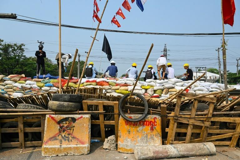Protesters sit on a makeshift barricade erected to deter security forces in Yangon