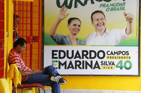 Members of a campaign committee are pictured next to a campaign sign of the late presidential candidate Eduardo Campos and his vice-presidential candidate Marina Silva, in Recife