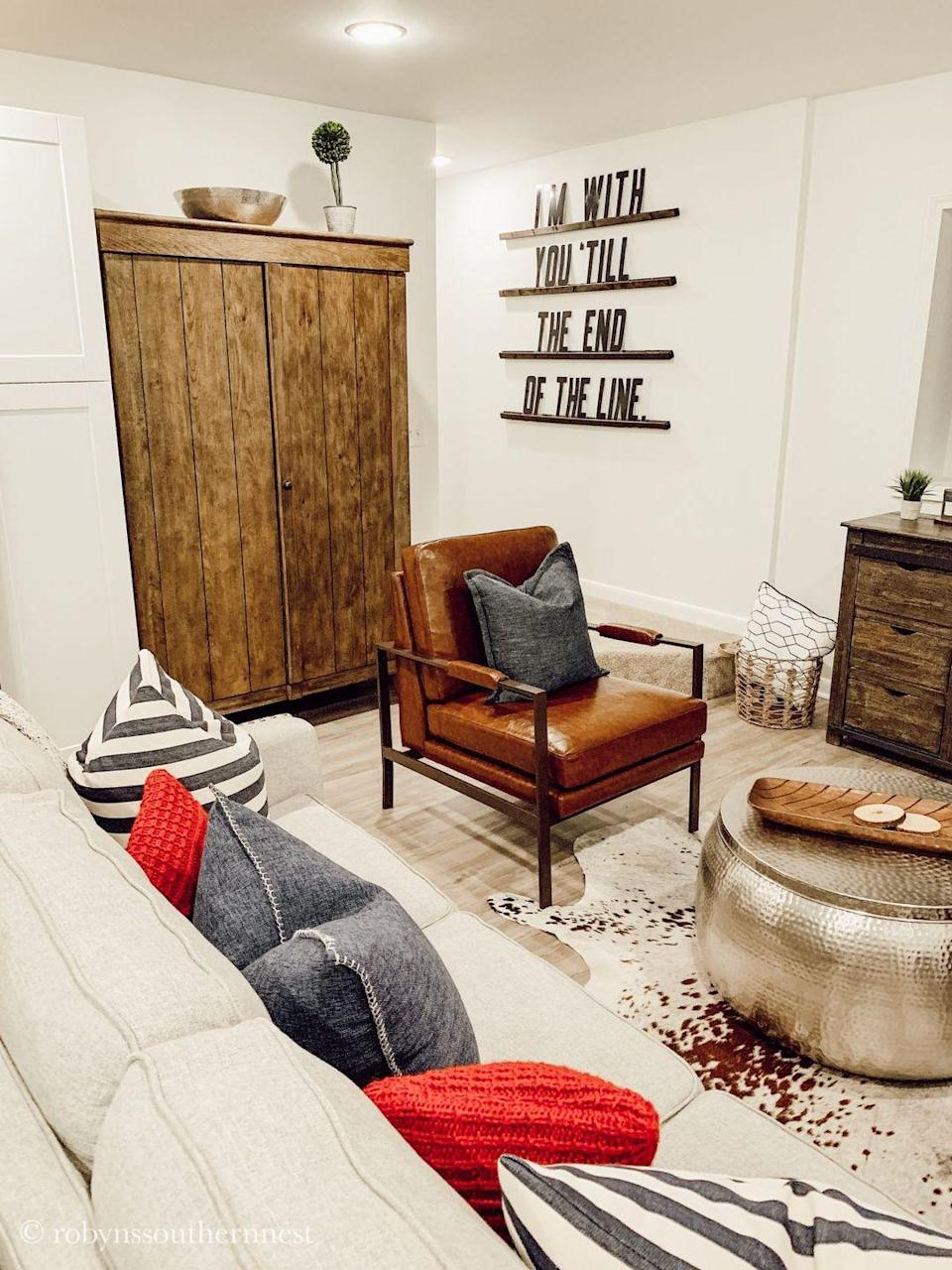 """<p>Natural materials, a custom barn door, and a decorative wagon wheel bring rustic chic style to this basement space. Use romantic word wall art to celebrate your love as well as your style.</p><p><strong>See more at <a href=""""https://www.robynssouthernnest.com/2019/07/16/basement-renovation-reveal/"""" rel=""""nofollow noopener"""" target=""""_blank"""" data-ylk=""""slk:Robyn's Southern Nest"""" class=""""link rapid-noclick-resp"""">Robyn's Southern Nest</a>. </strong></p><p><a class=""""link rapid-noclick-resp"""" href=""""https://go.redirectingat.com?id=74968X1596630&url=https%3A%2F%2Fwww.walmart.com%2Fip%2FMetal-Cutout-Home-Sweet-Home-Cursive-Cutout-Sign-3D-Word-Art-Home-Accent-Decor-Perfect-for-Modern-Rustic-or-Vintage-Farmhouse-Style-by-Lavish-Home%2F368072870&sref=https%3A%2F%2Fwww.redbookmag.com%2Fhome%2Fg36061437%2Fbasement-ideas%2F"""" rel=""""nofollow noopener"""" target=""""_blank"""" data-ylk=""""slk:SHOP WORD WALL ART"""">SHOP WORD WALL ART</a></p>"""