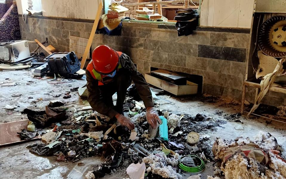 A rescue worker examines remains at the site of a blast at a religious school in Peshawar - AFP