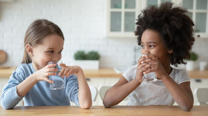 Two young girls sit at a table drinking glasses of water while smiling at each other.