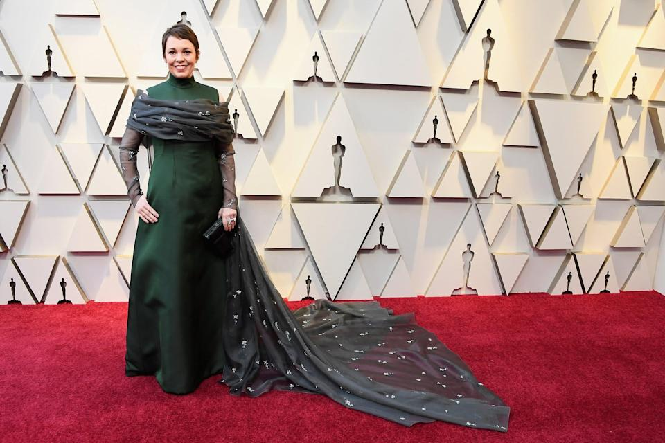 <p>Wearing a deep-green gown with a floor-skimming train and Chopard jewels.</p>