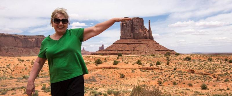 Forced perspective of a senior adult woman (60s) pretending to touch a famous rock formation in Utah Monument Valley