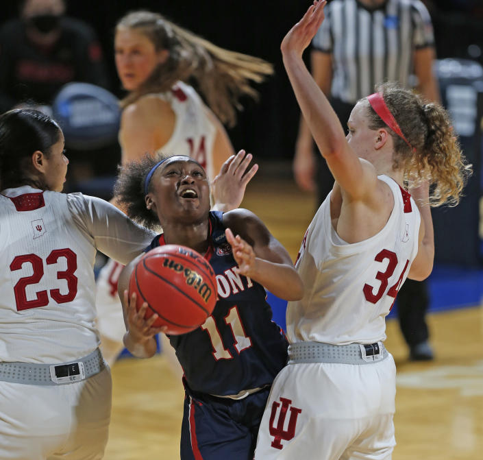 Belmont guard Destinee Wells (11) drives between Indiana guard Tori Campbell (23) and guard Grace Berger (34) during the first half of a college basketball game in the second round of the NCAA women's tournament at the Greehey Arena in San Antonio on Wednesday, March 24, 2021. (AP Photo/Ronald Cortes)
