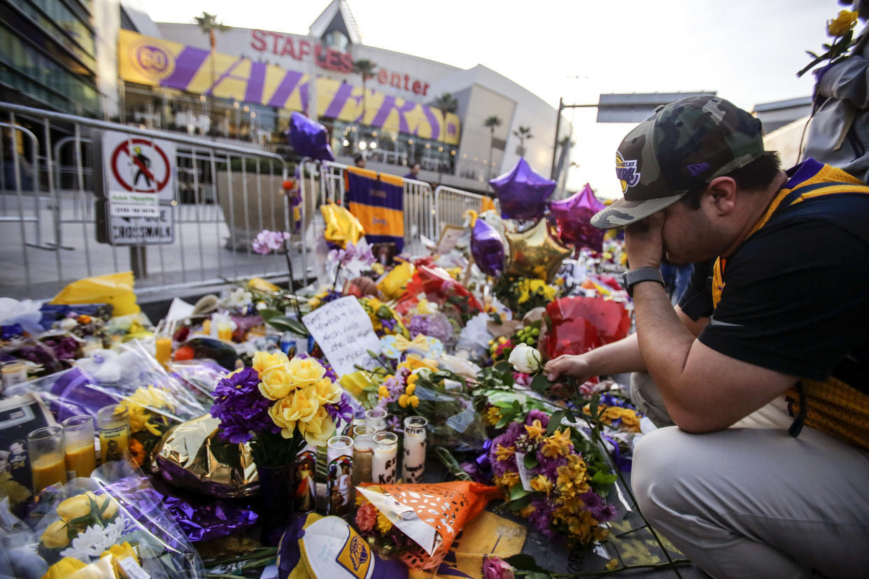 A fan pauses at a memorial to Kobe Bryant in front of Staples Center prior to an NBA game between the Los Angeles Lakers and the Portland Trail Blazers, Friday, Jan. 31, 2020, in Los Angeles. Bryant, the 18-time NBA All-Star who won five championships and became one of the greatest basketball players of his generation during a 20-year career with the Lakers, died in a helicopter crash Sunday. (AP Photo/Ringo H.W. Chiu)