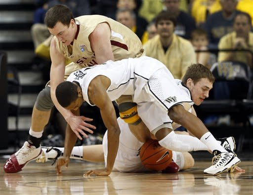 Boston College's Dennis Clifford, top, Wake Forest's Madison Jones, foreground, and Tyler Cavanaugh, right, scramble for control of a loose ball during the first half of an NCAA college basketball game in Winston-Salem, N.C., Saturday, Jan. 12, 2013. (AP Photo/Chuck Burton)