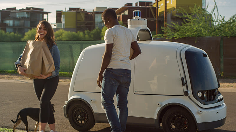 Two people retrieving grocery bags from a Nuro self-driving vehicle, a white box-shaped car with doors and a sensor array on top.