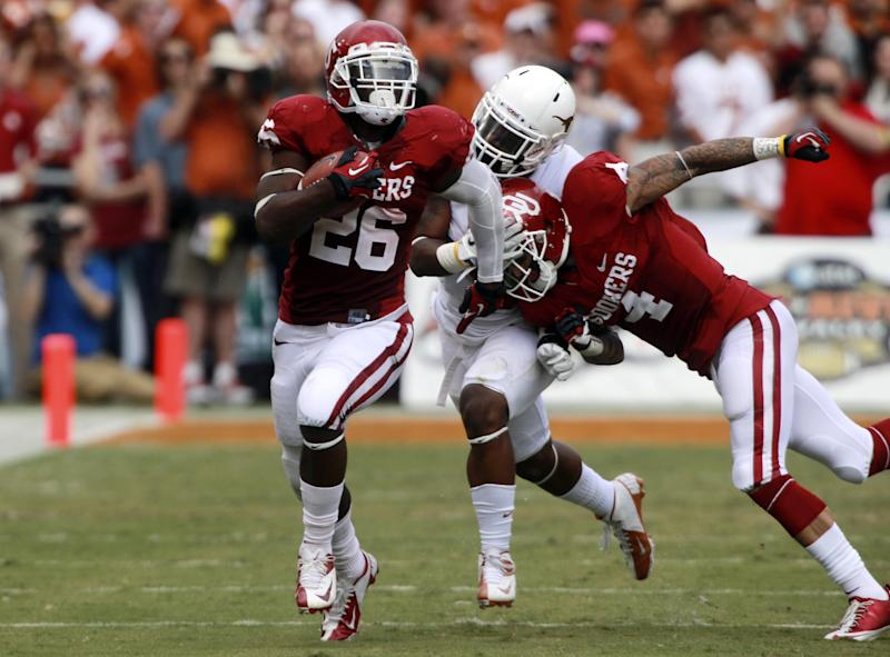 Oklahoma running back Damien Williams (26) breaks away for a touchdown run as teammate Kenny Stills (4) blocks Texas cornerback Quandre Diggs (6) during the first half of an NCAA college football game at the Cotton Bowl Saturday, Oct. 13, 2012, in Dallas. (AP Photo/Michael Mulvey)
