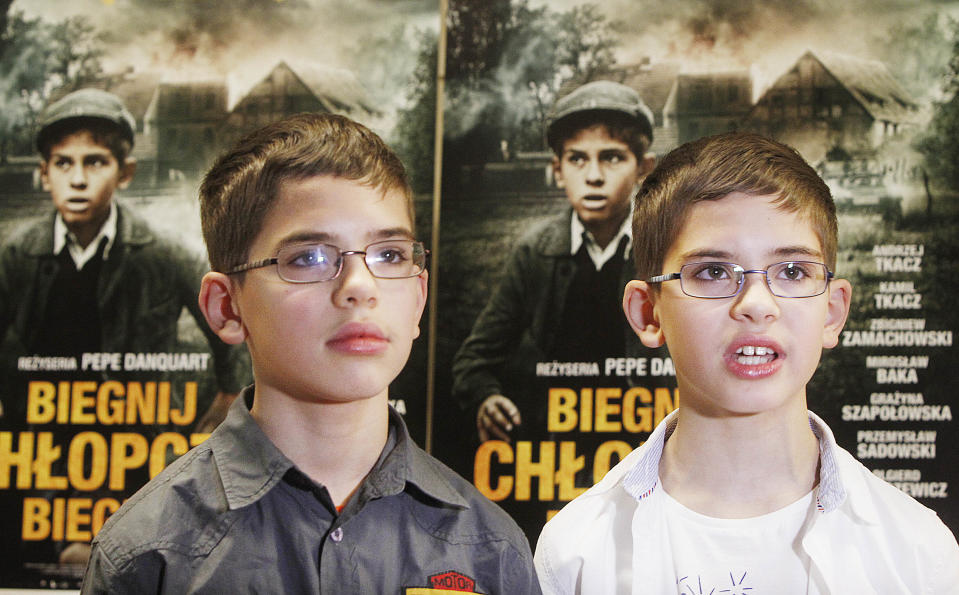 """Actors, twin brothers Andrzej ,left,and Kamil Tkacz who play the role of young Yoram Friedman, a Jewish boy struggling to survive the Holocaust in the woods near Warsaw, with occasional help from local farmers but also facing their indifference, hatred and betrayal. The movie """"Run, Boy, Run"""" by German director Pepe Danquart premiers at the Jewish History Museum in Warsaw, Poland, on Wednesday, Jan. 8, 2014. (AP Photo/Czarek Sokolowski)"""