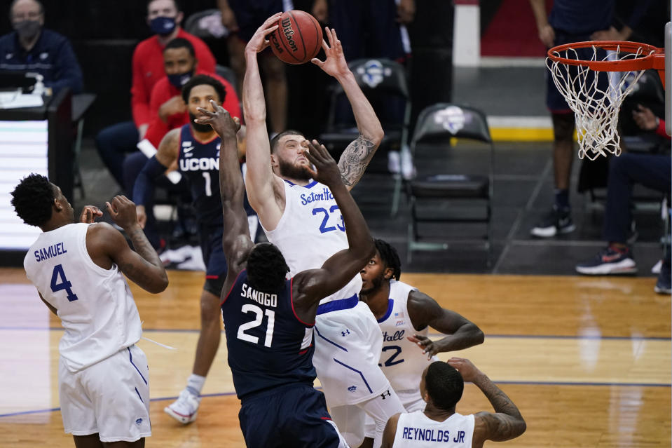 Seton Hall forward Sandro Mamukelashvili (23) grabs the ball in front of Connecticut forward Adama Sanogo (21) as Seton Hall forward Tyrese Samuel (4) and Connecticut guard R.J. Cole (1) watch during the second half of an NCAA college basketball game Wednesday, March 3, 2021, in Newark, N.J. (AP Photo/Kathy Willens)