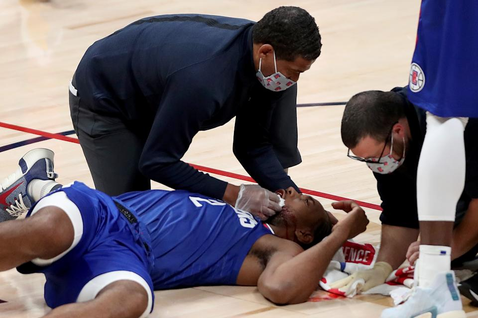 Kawhi Leonard #2 of the Los Angeles Clippers is attended to after being injured against the Denver Nuggets in the fourth quarter at Ball Arena.