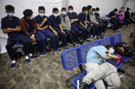 FILE - In this March 30, 2021, file photo, young unaccompanied migrants wait for their turn at the secondary processing station inside the U.S. Customs and Border Protection facility, the main detention center for unaccompanied children in the Rio Grande Valley, in Donna, Texas. The number of unaccompanied children encountered on the U.S. border with Mexico in April 2021 eased from an all-time high a month earlier, while more adults are coming without families. Authorities encountered nearly 17,200 children traveling alone, down 9% from March but still far above the previous high in May 2019. (AP Photo/Dario Lopez-Mills, Pool, File)