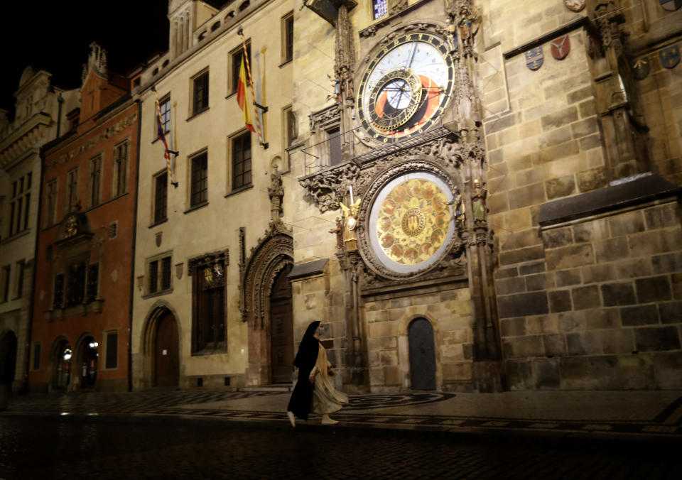 A nun walks past the Astronomical Clock on a near empty Old Town Square in Prague, Czech Republic, Friday, Oct. 23, 2020. In much of Europe, city squares and streets, be they wide, elegant boulevards like in Paris or cobblestoned alleys in Rome, serve as animated evening extensions of drawing rooms and living rooms. As Coronavirus restrictions once again put limitations on how we live and socialize, AP photographers across Europe delivered a snapshot of how Friday evening, the gateway to the weekend, looks and feels. (AP Photo/Petr David Josek)
