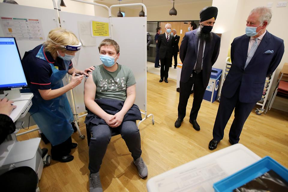 Britain's Prince Charles (R), Prince of Wales and Chief pharmacist Inderjit Singh (C) watch a vaccination taking place during a visit to the Queen Elizabeth Hospital in Birmingham, northern England on February 17, 2021. (Photo by MOLLY DARLINGTON / POOL / AFP) (Photo by MOLLY DARLINGTON/POOL/AFP via Getty Images)