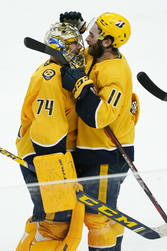 Nashville Predators center Luke Kunin (11) celebrates with goaltender Juuse Saros (74) after Kunin scored the winning goal against the Carolina Hurricanes during the second overtime in Game 4 of an NHL hockey Stanley Cup first-round playoff series Sunday, May 23, 2021, in Nashville, Tenn. The Predators won 4-3 to even the series 2-2. (AP Photo/Mark Humphrey)