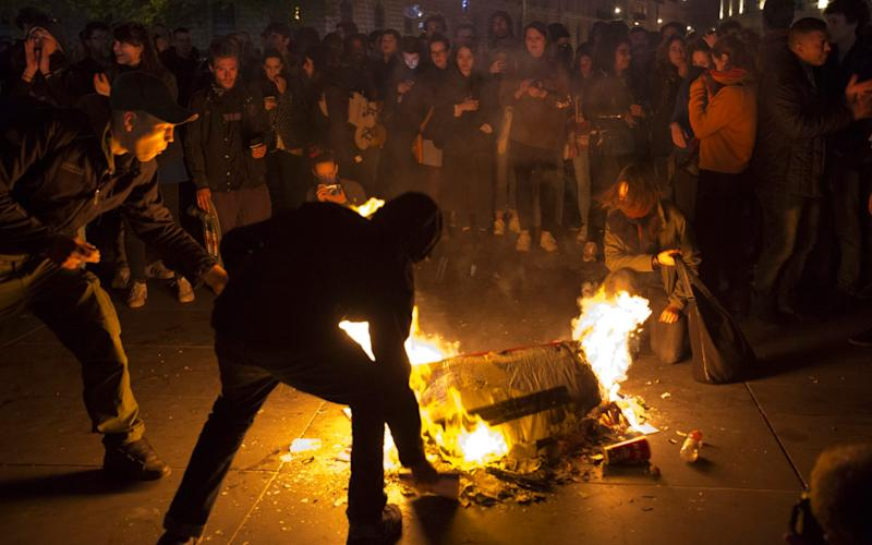 People burn litter as they protest in Paris - Credit: AP