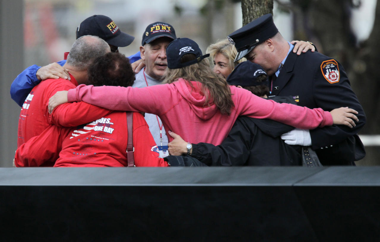 Visitors hug near a memorial pool at the National September 11 Memorial at the World Trade Center site in New York, Sunday, Sept. 11, 2011. (AP Photo/Seth Wenig, Pool)