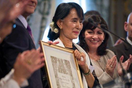 Myanmar pro-democracy leader Aung San Suu Kyi poses after receiving an honorary citizen award