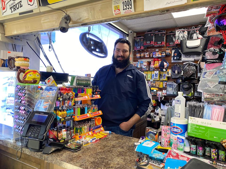 a man poses behind the cash register at a gas station
