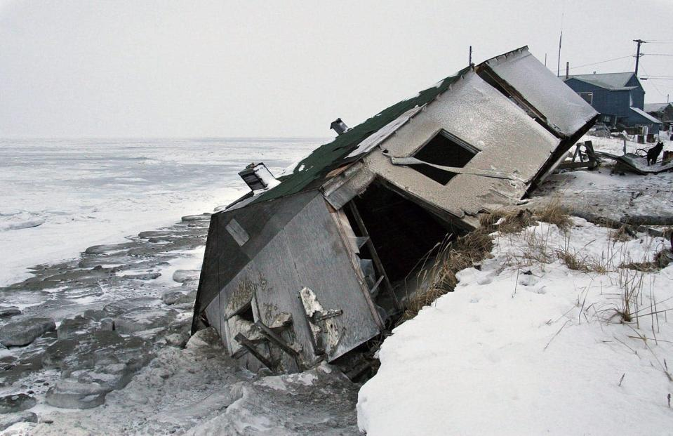 A single-storey house falling off a snow-covered shoreline into the ocean.