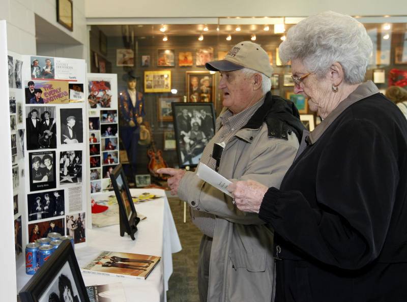 Everly Brothers fans Garnett, left, and Elizabeth Rhoades, right, of Central City, Ky, look over photos an memorabilia of the Everly Brothers before a memorial service to Phil Everly at the Merle Travis Music Center in Powderly, Ky, Saturday, Jan. 18, 2014. (AP Photo/John Sommers II)