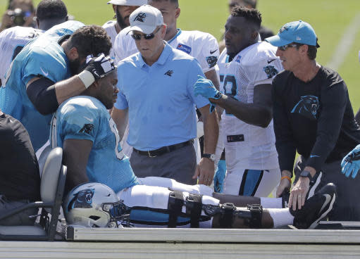 FILE - In this July 28, 2018, file photo, Carolina Panthers' Daryl Williams, center, is comforted by Matt Kalil, left, after getting injured during NFL football practice at the team's training camp in Spartanburg, S.C. Kalil becomes Carolina's third starting offensive lineman to go down with a knee injury. Right tackle Daryl Williams and left guard Amini Silatolu also are out with injuries. (AP Photo/Chuck Burton)