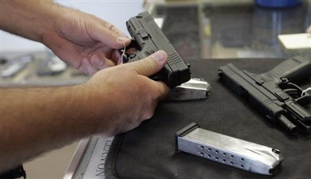 File photo of a customer inspecting a 9mm handgun at Rink's Gun and Sport in the Chicago, suburb of Lockport, Illinois