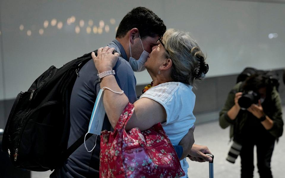 Karen Tyler greets and kisses her son Jonathan, who she's not seen for over a year and a half, as he arrives on a flight from Houston, Texas - Matt Dunham