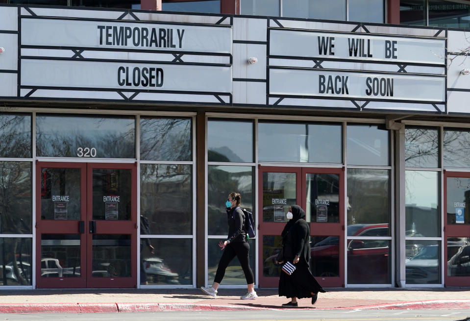 Shoppers pass a theater closed due to the COVID-19 outbreak, Wednesday, March 3, 2021, in San Antonio. Gov. Greg Abbott says Texas is lifting a mask mandate and lifting business capacity limits next week. (AP Photo/Eric Gay)