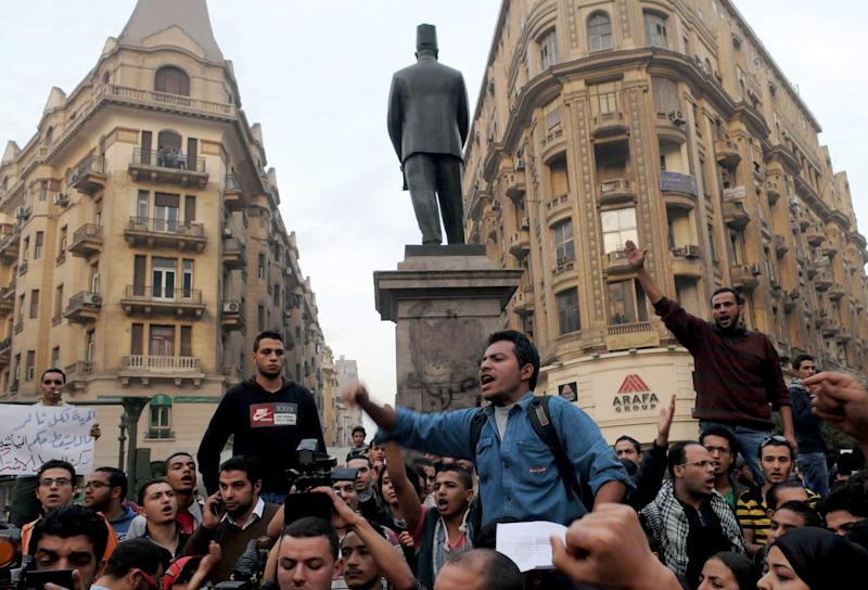 Protesters chant slogans in Talaat Harb Square in Cairo, Egypt, against the issuance of a new law regulating demonstrations, Wednesday, Nov. 27, 2013. Nearly two dozen women, some as young as 15, are handed heavy prison sentences for protesting in support of Egypt's ousted Islamist president, a harsh verdict that comes a day after police beat and terrorized prominent female activists in a crackdown on secular demonstrators. Critics warn that military-backed authorities who have assumed power are becoming bolder in silencing dissent, with abuses reminiscent of the Hosni Mubarak era. (AP Photo/Mohammed Asad)