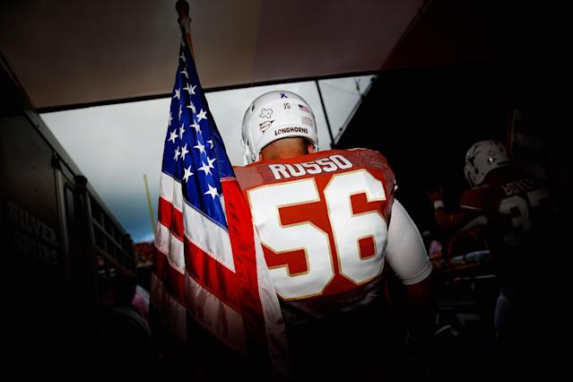 DALLAS, TX - OCTOBER 12: Drew Russo #56 of the Texas Longhorns carries an American flag as he takes the field against the Oklahoma Sooners at the Cotton Bowl on October 12, 2013 in Dallas, Texas. (Photo by Tom Pennington/Getty Images)