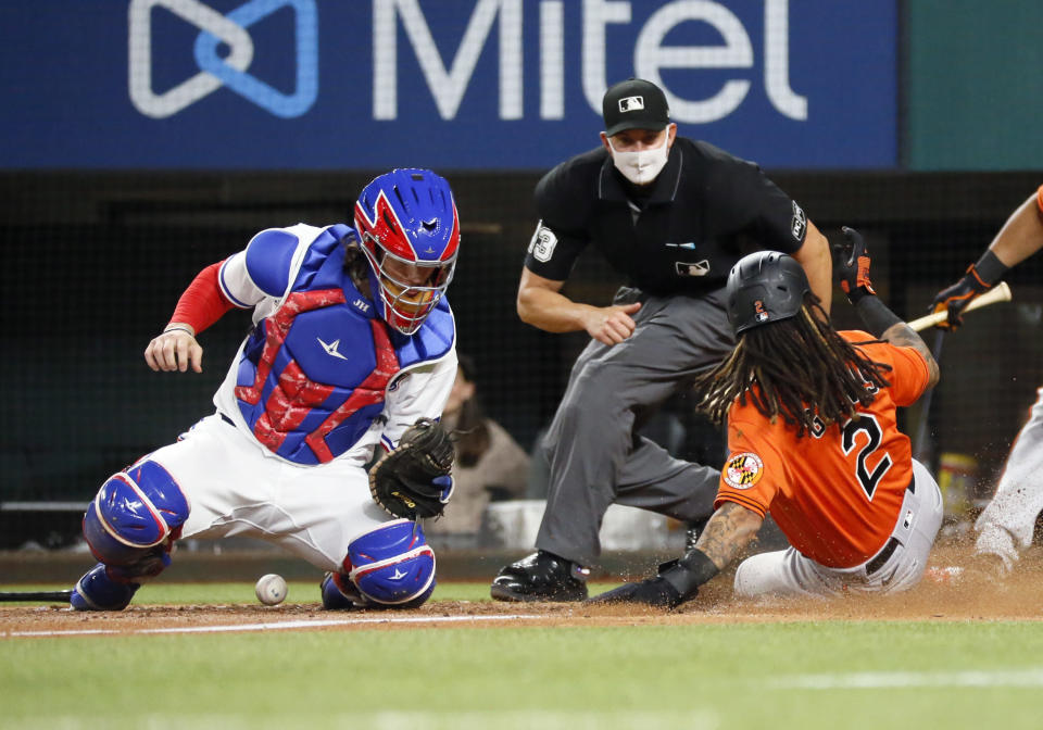 Baltimore Orioles' Freddy Galvis, right, slides home safely as Texas Rangers catcher Jonah Heim, left, cannot handle the throw as umpire Shane Livensparger, center, looks on during the seventh inning of a baseball game in Arlington, Texas, Saturday, April 17, 2021. (AP Photo/Ray Carlin)