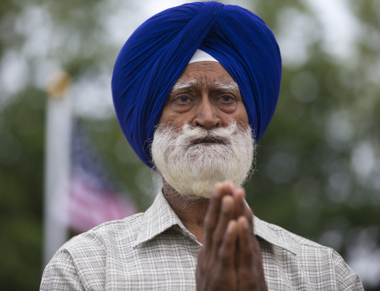 A man prays outside the Sikh Temple of Wisconsin in Oak Creek, Wis., Sunday, Aug. 12, 2012. More than 100 people gathered for the first Sunday prayer service since a white supremacist shot and killed six people there before fatally shooting himself. (AP Photo/Jeffrey Phelps)