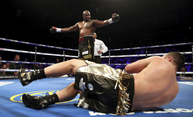 Dillian Whyte, top, knocks down Joseph Parker during their heavyweight bout at the O2 Arena in London, Saturday, July 28, 2018. (Nick Potts/PA via AP)