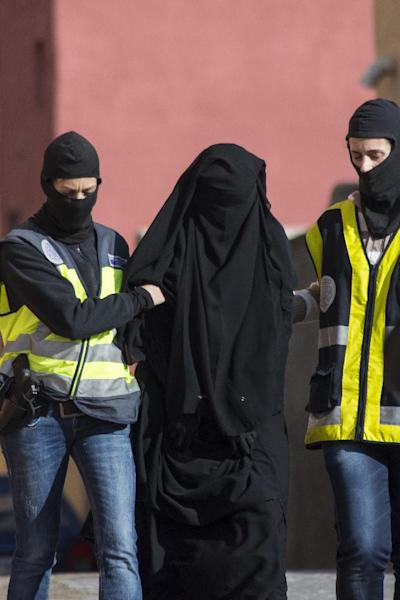 Spanish police escort a 20-year-old Abaya clad woman in Melilla on December 16, 2014 during a series of arrests for suspected recruitment of young women via the Internet to join Islamic State militants fighting in Iraq and Syria (AFP Photo/Jesus Blasco de Avellaneda)