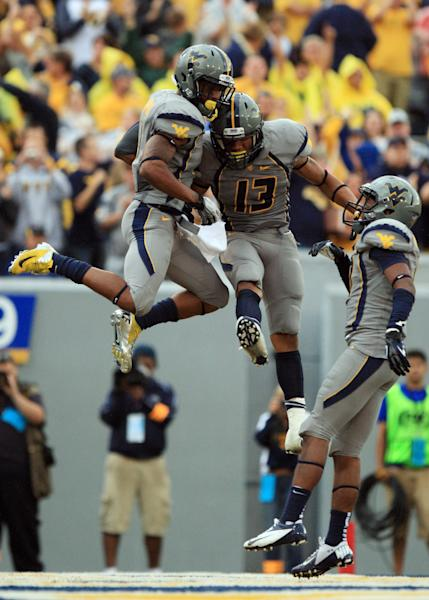 West Virginia players, from left, Tavon Austin, Andrew Buie and Stedman Bailey celebrate Austin's touchdown during an NCAA college football game against the University of Maryland in Morgantown, W.Va., Saturday, Sept. 22, 2012. (AP Photo/Christopher Jackson)