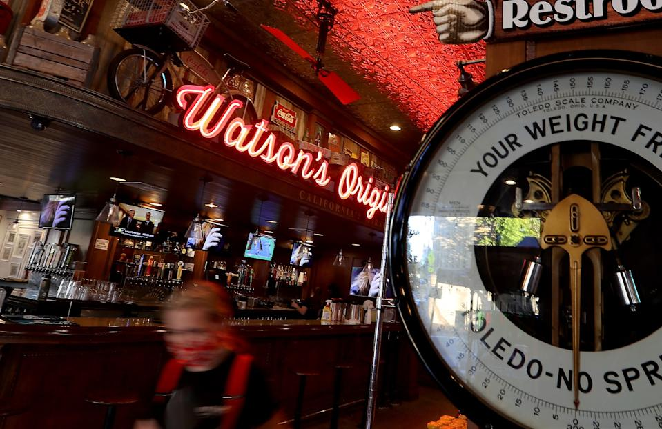 A server wears a protective mask at Watson's Original Soda Fountain in downtown Orange.