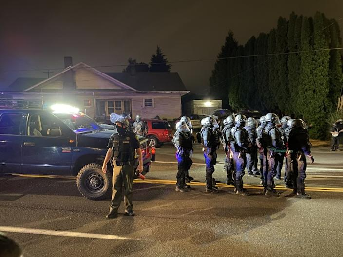 """After declaring an unlawful assembly late Sunday in a northeast Portland, Ore., neighborhood, Multnomah County sheriff's deputies line up to clear Black Lives Matter protesters off a street near a police precinct. <span class=""""copyright"""">(Richard Read / Los Angeles Times)</span>"""