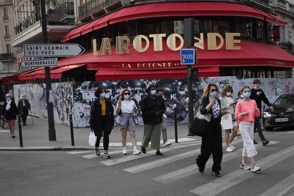 """Parisians walk home just before the 19h00 curfew in front of the closed Rotonde restaurant, in Paris, Thursday, April 1, 2021. France's prime minister Jean Castex on Thursday defended new nationwide measures to combat a resurgent coronavirus in France that include closing schools for at least three weeks and putting in place a month-long domestic travel ban, the government has acted """"consistently and pragmatically"""".(AP Photo/Francois Mori)"""