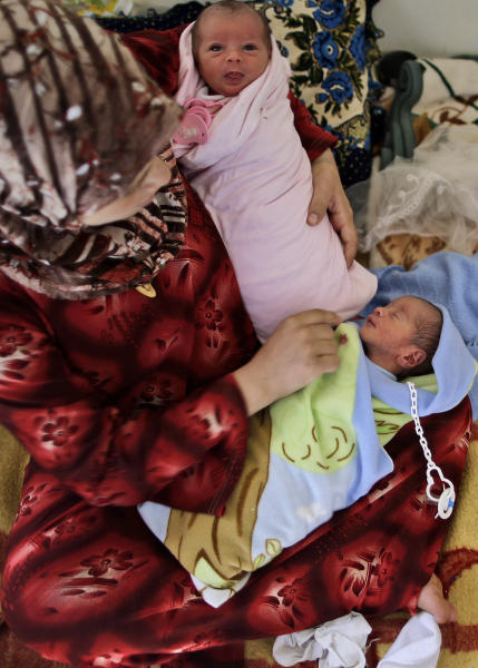 In this Friday,Sept. 7, 2012, photo, Fatimah Abdullah, 29, who fled her home in Marea 15 days ago, due to Syrian government shelling, holds her 4 days old twin Ahmad and Bayan, who were born in a Turkish hospital and brought back with her to the border where they take refuge at the Bab Al-Salameh border crossing, in hopes of entering one of the refugee camps in Turkey, near the Syrian town of Azaz. Despite rising international concern and new pledges of aid, the plight of Syria's internally displaced is growing worse as fighting shows no signs of slackening and more head for the borders. Syria's neighbors are reluctant to take in more refugees, leaving thousands, at least half young children, stranded on the borders with poor hygiene and insufficient food. At the Bab al-Salameh border crossing there are already an estimated 5,000 refugees hoping to cross into Turkey, which already hosts 80,000 Syrians and isn't allowing more in for now. (AP Photo/Muhammed Muheisen)