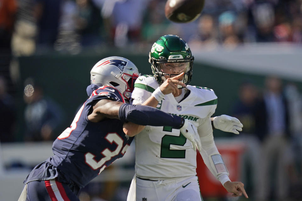 New York Jets quarterback Zach Wilson, right, throws under pressure from New England Patriots' Joejuan Williams during the second half of an NFL football game, Sunday, Sept. 19, 2021, in East Rutherford, N.J. (AP Photo/Frank Franklin II)